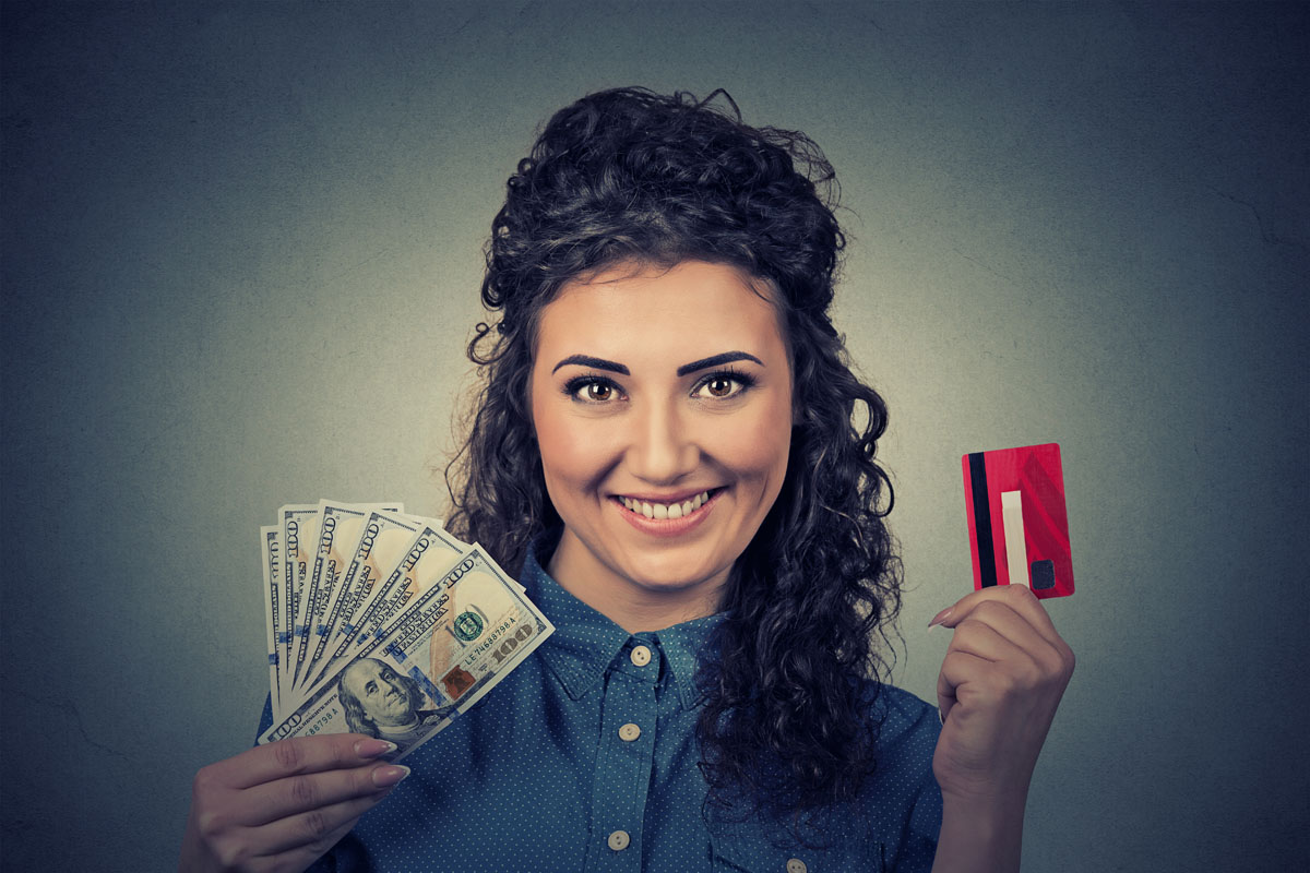 woman holding showing credit card and cash dollar banknotes bill